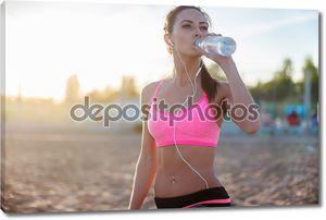 Красивая фитнес спортсмен женщина питьевой водой после работы, осуществляя на пляже летний вечер в солнечный Солнечный открытый портрет