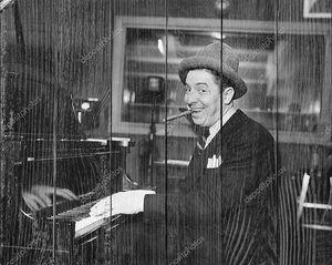 Человек с сигарой во рту играет на фортепиано