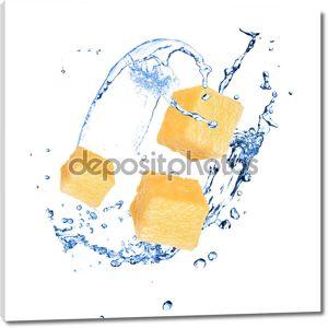 Кусочки ананаса с плеск воды над белой