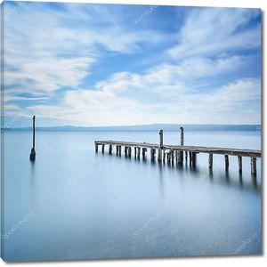 деревянный пирс или причал остается на голубое озеро. длинные выдержки.