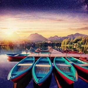 Лодка на скамье подсудимых в окружении гор, звездное небо