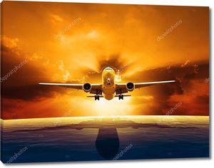 пассажирский реактивный самолет, пролетающий над красивым уровнем моря с закатом