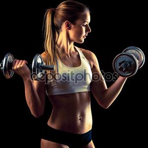 Фитнес девушка - привлекательная молодая женщина, работают с гантелями