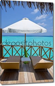 зонтик и шезлонг лаунджа на террасе виллы воды, Мальдивы.