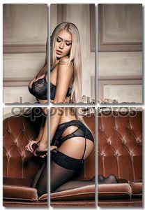 Сексуальная женщина в соблазнительной черное белье, сидя на диване в чулках