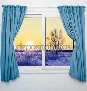 Окно с занавесками с видом на закат