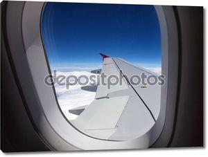 Окно самолета - полет над облаками