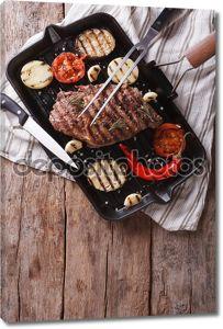 стейк на гриле говядины в сковороду с овощами. Вертикальный вид сверху