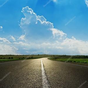 Крупным планом асфальта дороги под пасмурное голубое небо