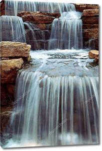 Водопад падает  на природные камни