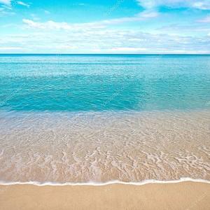 Красивый песчаный пляж с спокойной воде против голубого неба.