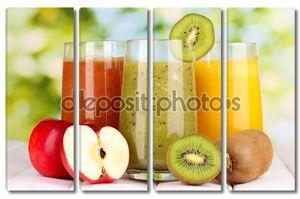свежие фруктовые соки на деревянном столе, на зеленом фоне