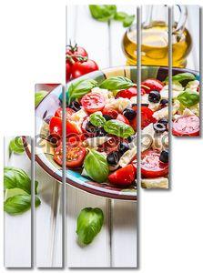 Caprese. Caprese salad. Italian salad. Mediterranean salad. Italian cuisine. Mediterranean cuisine. Tomato mozzarella basil leaves black olives and olive oil on wooden table.