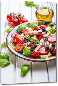 Caprese. Caprese salad. Italian salad. Mediterranean salad. Italian cuisine. Mediterranean cuisine. Tomato mozzarella basil leaves black olives and olive oil on wooden table.