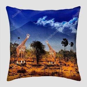 Два жирафа в саванне на фоне гор