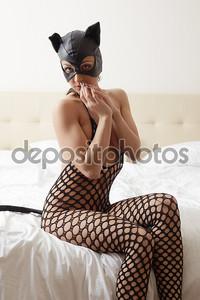 Модели рекламирует костюм Женщины-кошки в гостиничном номере