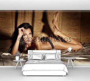Молодая сексуальная женщина в нижнем белье, лежа в постели, расслабляющий