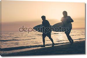 Два мальчика с досками для серфинга на закате
