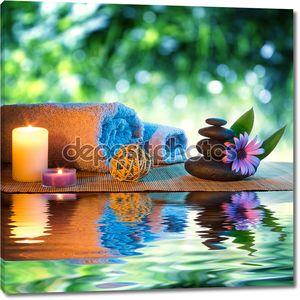 Две свечи и полотенца черные камни и фиолетовый ромашка на воде
