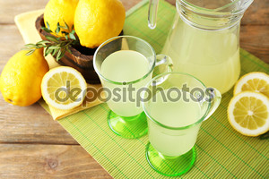 Натюрморт с лимонным соком и нарезанные лимоны на цвет ковра, крупным планом