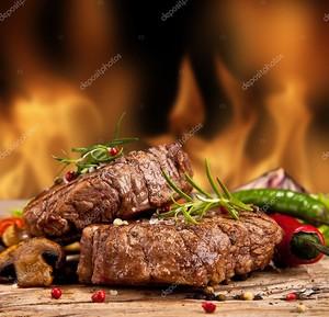 Два стейка на пламенном фоне