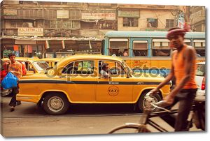 Yellow taxi car, buses and cyclists driving on the busy street of indian city