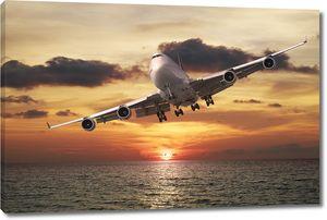 Вечерний рейс. Реактивный самолет над морем на закате.