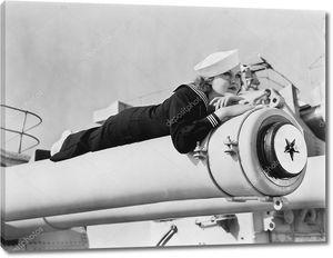 Девушка в морской форме лежа на пушке