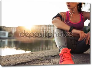 Young woman runner resting along pond