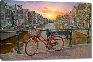 Оранжевый велосипед в центре города Амстердам в Нидерландах на закате