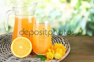 стакан и кувшин апельсинового сока на деревянном столе, на зеленом фоне