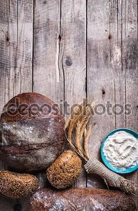 Деревенский хлеб, пшеница и мука на деревянных фоне