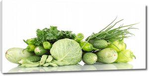 Различные зеленые овощи на белом столе