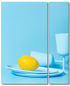 Лимон на голубой тарелке с бокалами