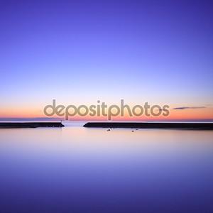 Бетон пирса силуэт и синий океан на Сумерки закат