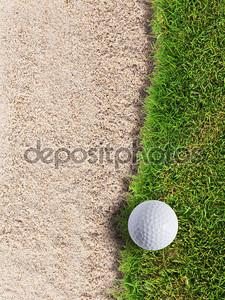 Мяч для гольфа на зеленой траве около песка бункер